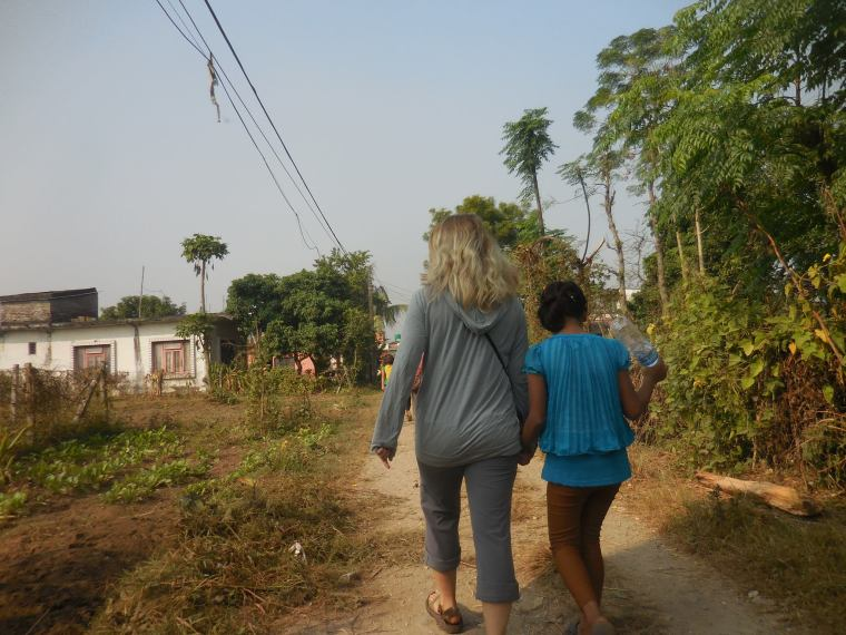 Monika in Nepal with Jaminah, one of the orphaned children that Monika spent time with in Nepal. Here they are walking to the new school that the group Monika was in Nepal with raised money to pay for the kids to go to. Photo courtesy of Monika Fleming.